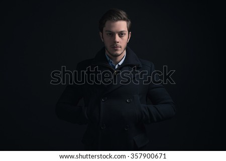 Young man with stubbly beard wearing dark blue winter jacket. - stock photo