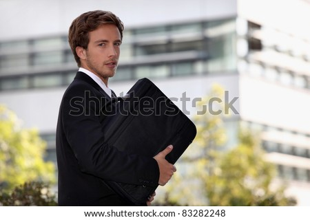 Young man with suitcase going to work - stock photo