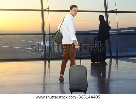 Young man with suitcase in hall of airport - stock photo