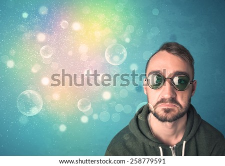 Young man with sunglasses and bokeh colourful lights concept - stock photo