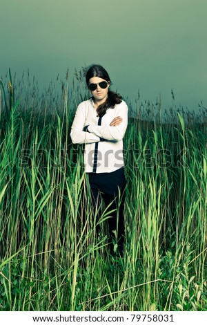 Young man with sunglasses and long brown hair standing in field with long grass. Stormy cloudy sky.