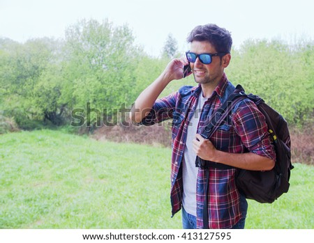 Young man with sunglasses carrying a bag and talking on the mobile phone. There is a green field as background.