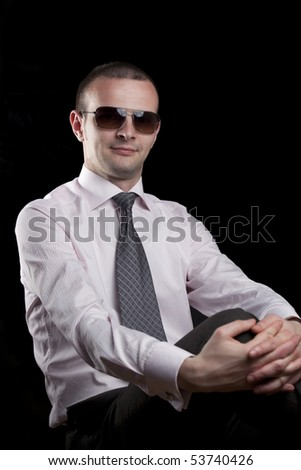 Young man with sunglasses posing on a black background - stock photo