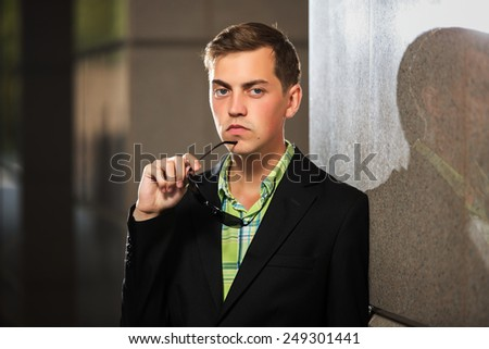Young man with sunglasses standing at the wall - stock photo