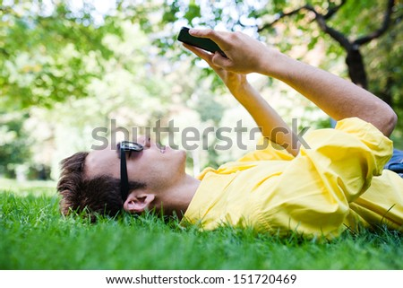 Young man with sunglasses texting on the grass - stock photo