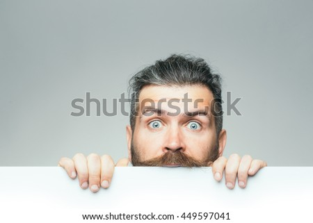 young man with surprised face with long hair behind white paper sheet in studio on grey background, copy space