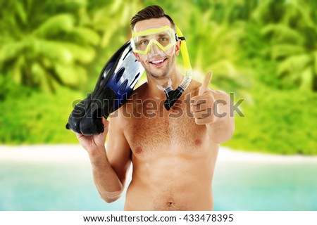Young man with swimming mask or goggles with flippers on blurred resort background - stock photo