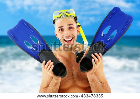 Young man with swimming mask or goggles with flippers on blurred sea background - stock photo