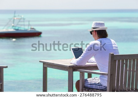 Young man with tablet computer during tropical beach vacation - stock photo