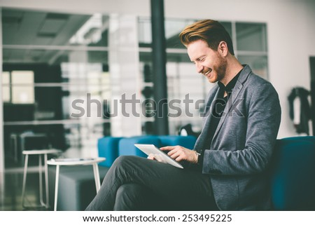 Young man with tablet in the office - stock photo
