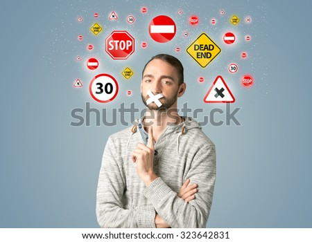 Young man with taped mouth and traffic signals around his head   - stock photo
