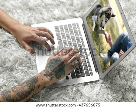 Young man with tattoo using laptop on a floor at home - stock photo