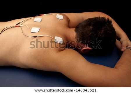 Young man with TENS on his back - stock photo