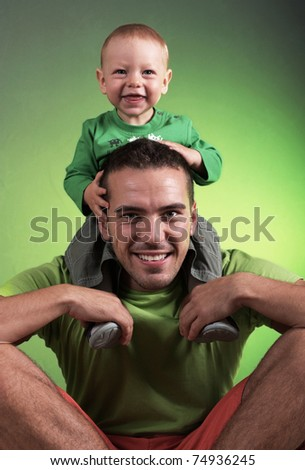 Young man with the child up on shoulder - stock photo