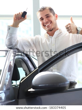 young man with the keys of his new car and Thumbs Up in the showroom  - stock photo