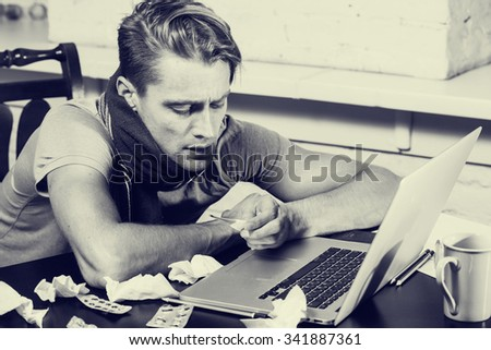 Young man with thermometer sick blowing his nose in his living room working notebook black and white  - stock photo