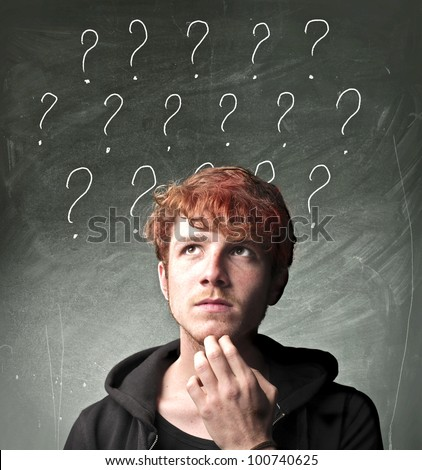 Young man with thoughtful expression and question marks over his head - stock photo