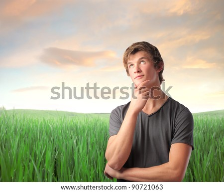 Young man with thoughtful expression on a green meadow - stock photo
