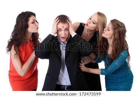 Young man with three girls and lipstick kiss-marks - stock photo