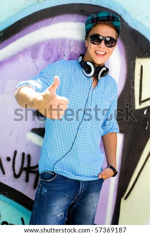 Young man with thumbs up - stock photo