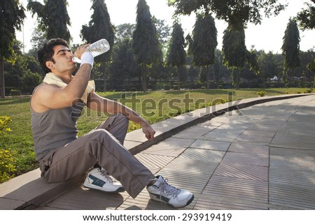 Young man with towel round shoulders drinking water after workout - stock photo