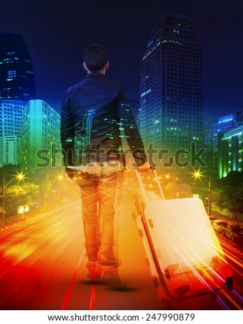young man with traveling luggage against  lighting of urban scene and colorful of city life - stock photo