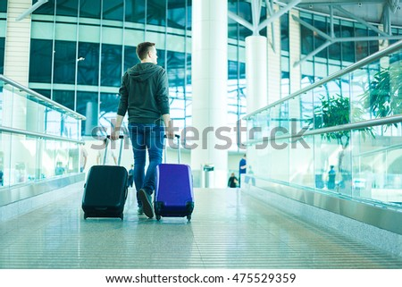 Young man with two cabin size bags in the airport