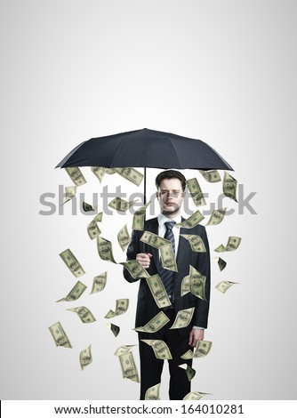 young man with umbrella and dollars rain - stock photo