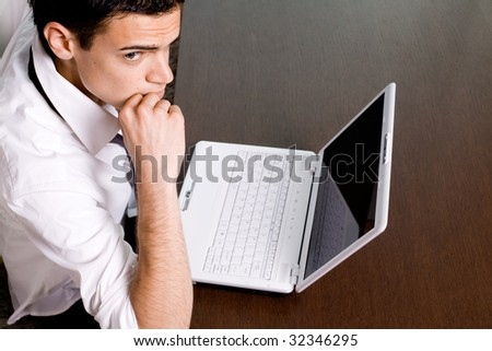 Young man with white laptop computer working and thinking
