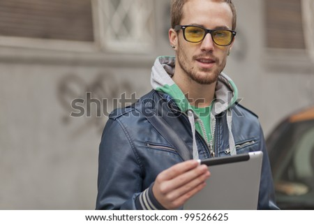 Young man with yellow glasses use tablet computer on street, public space. Blurred background - stock photo