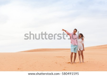 Young Man Woman In Desert Beautiful Couple Asian Girl And Guy Point Finger Embrace Sand Dune Landscape Background