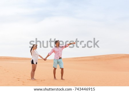 Young Man Woman In Desert Beautiful Couple Asian Girl And Guy Point Finger Sand Dune Landscape Background