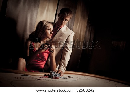 Young man & woman playing poker in casino - stock photo