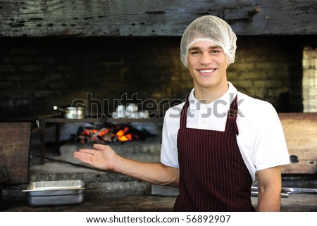 Young man working at a restaurant showing wood-fired oven - stock photo