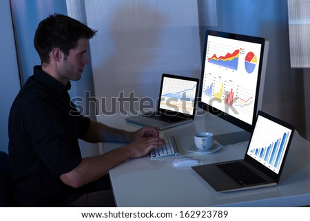 Young man working at computer in the office at night - stock photo
