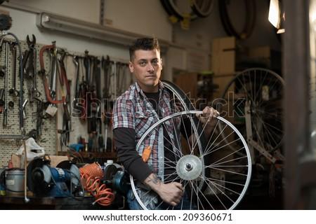 Young man working in a biking repair shop - stock photo