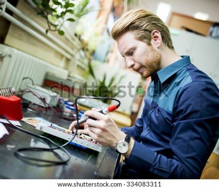 Young man working in electronics workshop