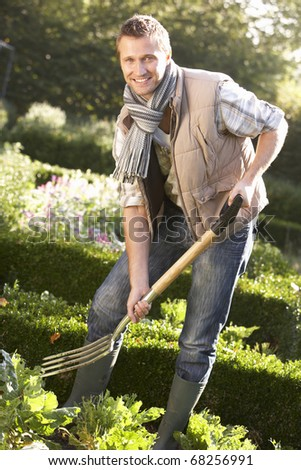Young man working in garden - stock photo