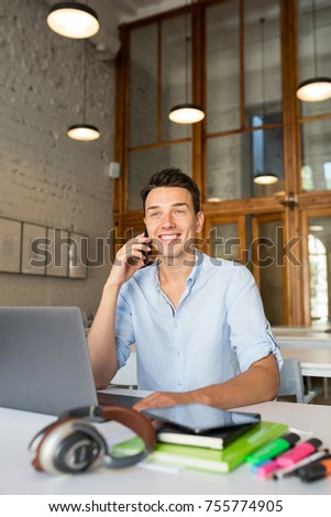 young man working in office room at laptop, smiling, start up, talking on phone