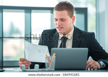 Young man working in office with laptop - stock photo