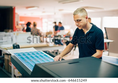 Young man working in printing factory. Printing Press