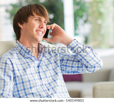 Young Man Working On Cell Phone, Indoors - stock photo