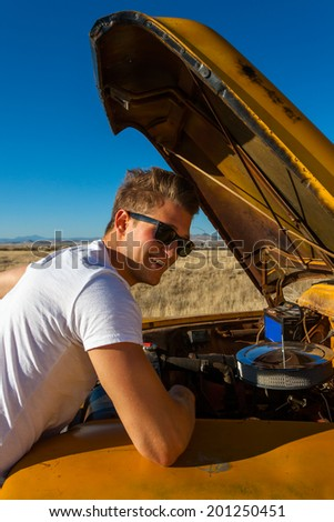 Young man working on classic truck  - stock photo