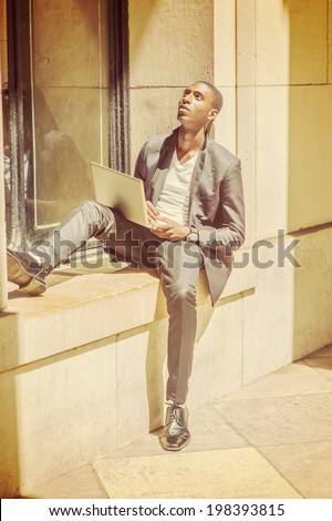 Young Man Working on Computer. Wearing a white under wear, fashionable jacket, pants, shoes, a computer on lap, a young black college student is sitting against a window frame, looking up, thinking. - stock photo