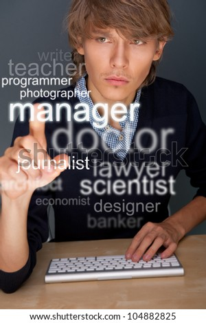 Young man working on his computer and looking for staff or a job. Choosing profession on transparent touchscreen - stock photo