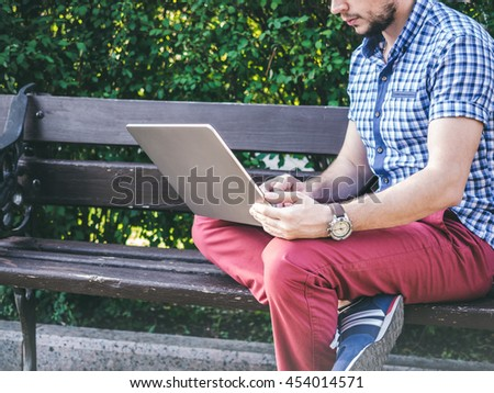 Young Man working on his laptop sitting on the bench in park - stock photo
