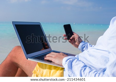 Young man working on laptop at tropical beach - stock photo