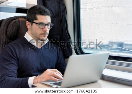 young man working on laptop computer on the train - stock photo
