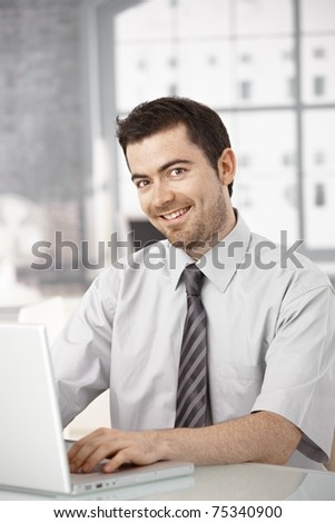 Young man working on laptop in bright office sitting at desk.? - stock photo