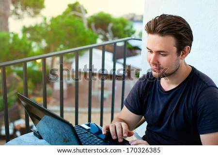 Young man working on laptop with outdoors view. - stock photo